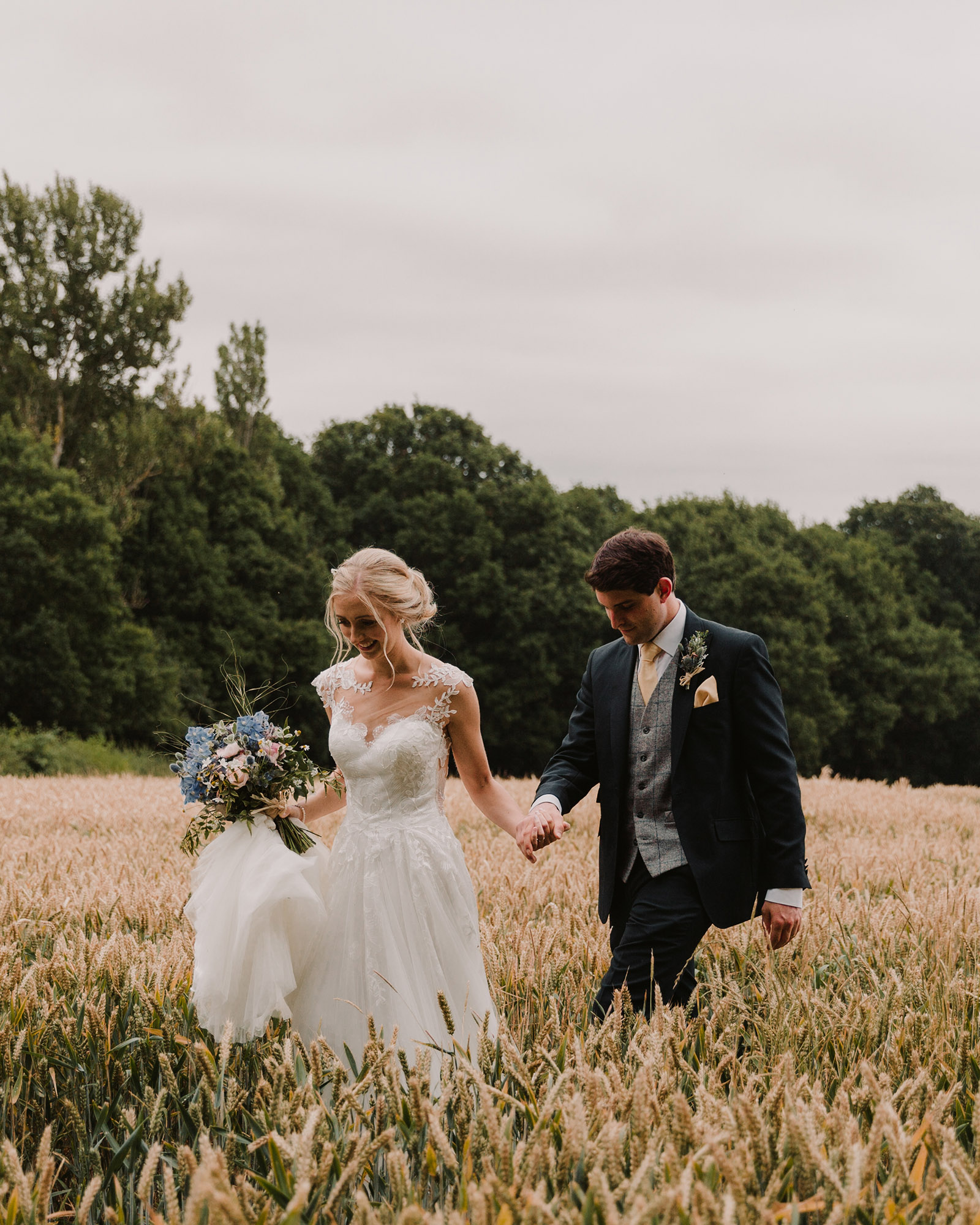 Beautiful Wedding Couple walking through a field