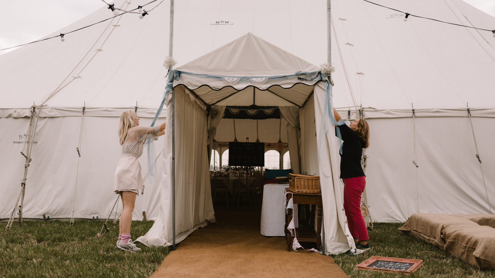 Bride and mother fixing tent