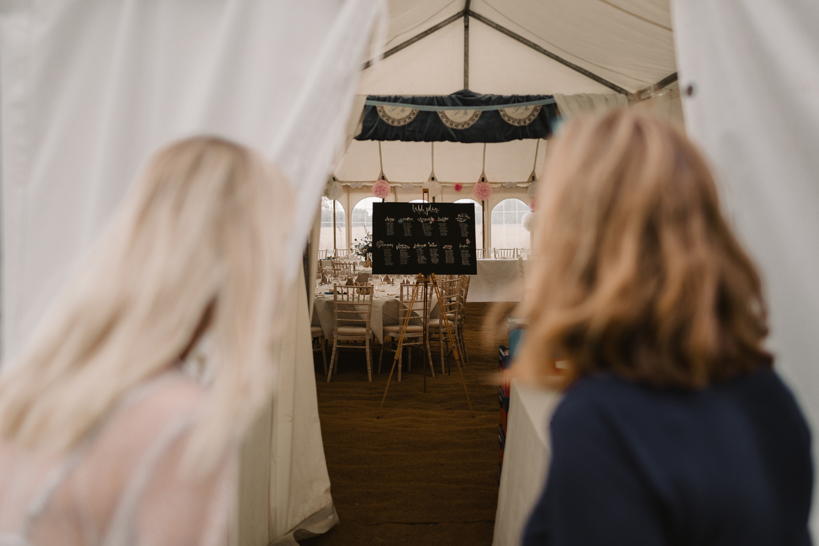 Bride and mother looking inside marquee