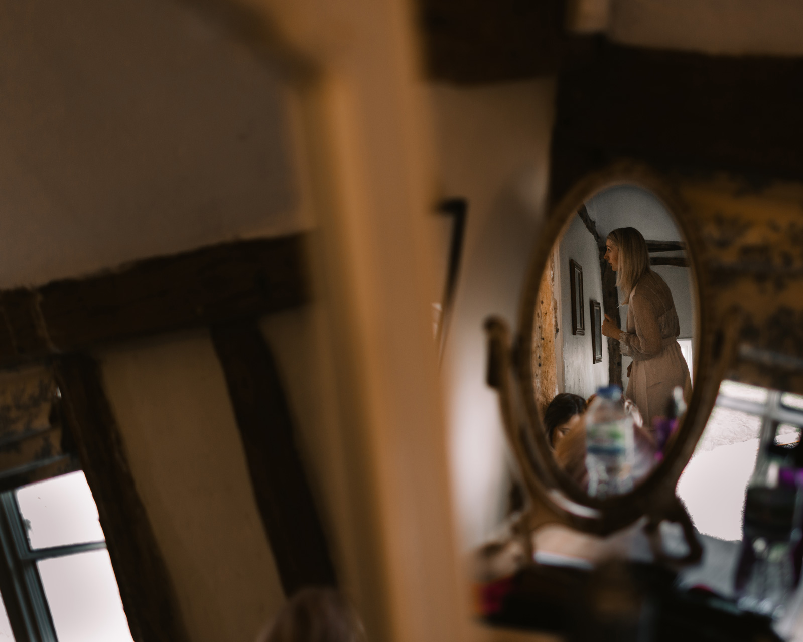 Reflection of bride in oval mirror