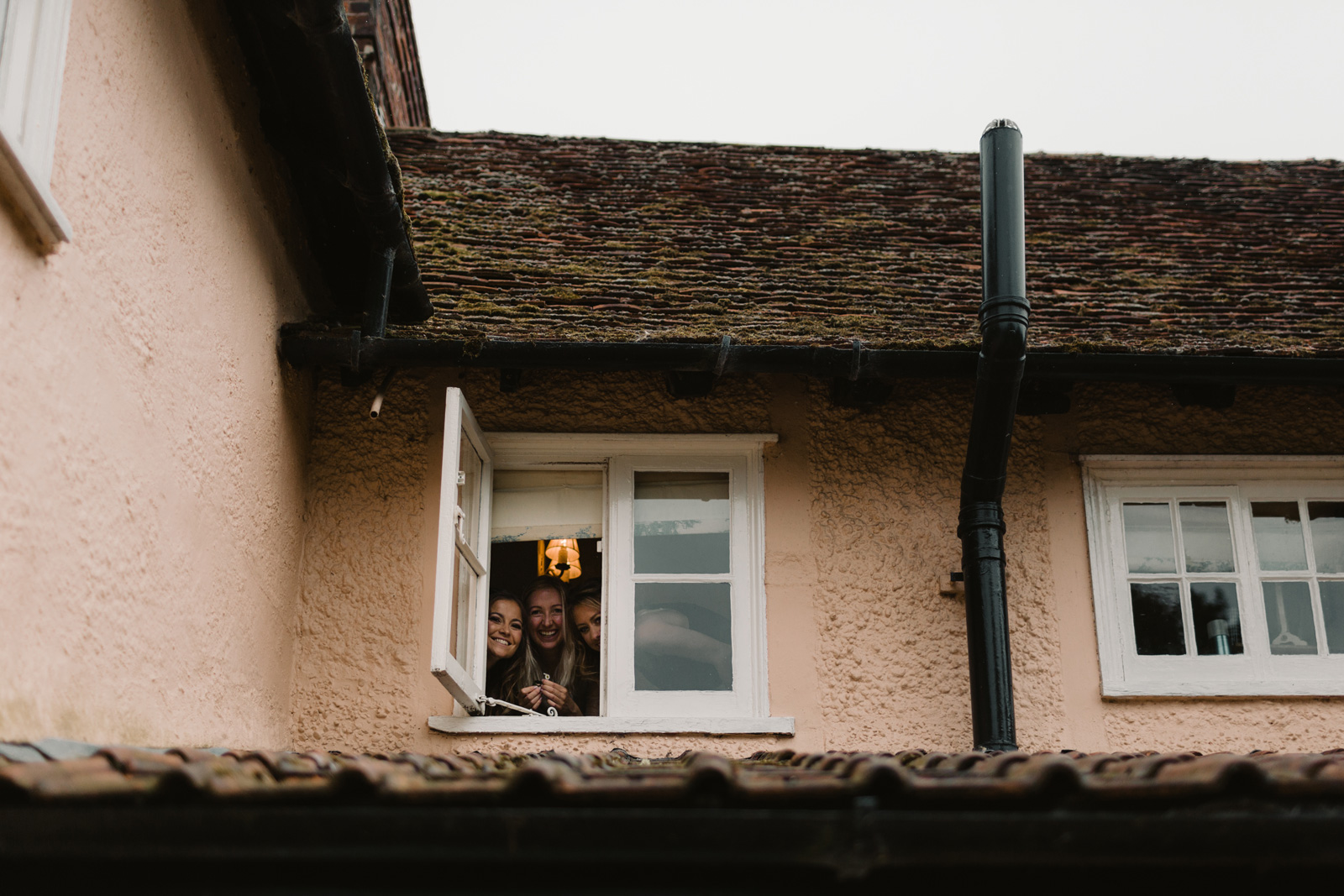 Photo of 3 bridesmaids smiling through a small window