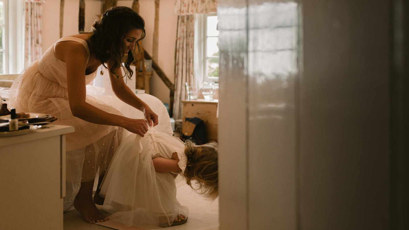Photo of Bridesmaid tying up back of Daughters dress